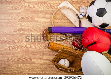 sports equipment on a gym floor, football, hockey, rugby, baseball, cricket, boxing, badminton and squash. - stock photo