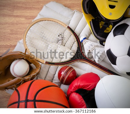 sports equipment on a gym floor, football, rugby, baseball, cricket, basketball, boxing, badminton, squash and helmet.