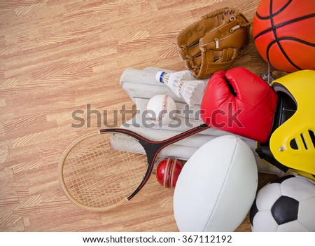 sports equipment on a gym floor, football, rugby, baseball, cricket, basketball, boxing, badminton, squash and helmet. landscape with copy space. - stock photo