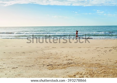 Sports. Fit Female Athlete Jogger Running On Beach. Sporty Athletic Woman Jogging During Workout Outside. Fitness, Exercising, Healthy Lifestyle. Health Concept - stock photo