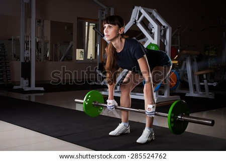 sports fitness girl with a barbell in the gym - stock photo