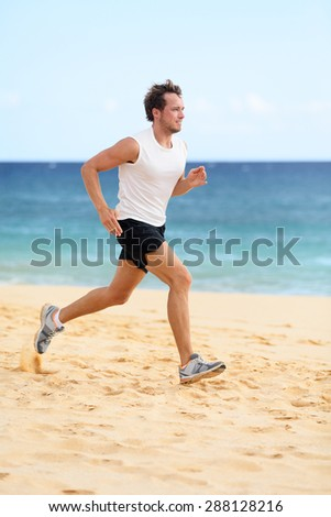 Sports fitness runner man running on beach. Handsome young fit sporty male athlete jogging outside on beautiful beach training in running shoes. Caucasian male model in his 20s working out.