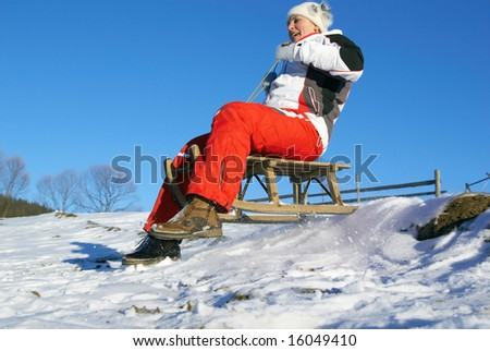 sports girl on sledge climbs down a mountain - stock photo