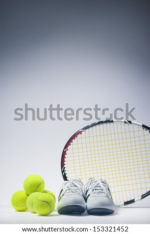 Sports Images Concepts: Tennis Raquet, Tennis Balls and Trainers against gray. vertical Image - stock photo