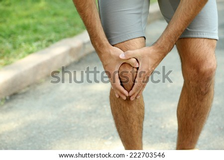 Sports injuries of man outdoors  - stock photo