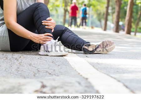 Sports injury. Woman with pain in ankle while jogging - stock photo