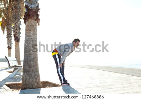 Sports man taking a break from exercising, stretching his legs while looking at sea. - stock photo