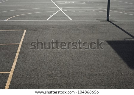Sports markings on asphalt school playground with shadow of basketball ring and space in bottom