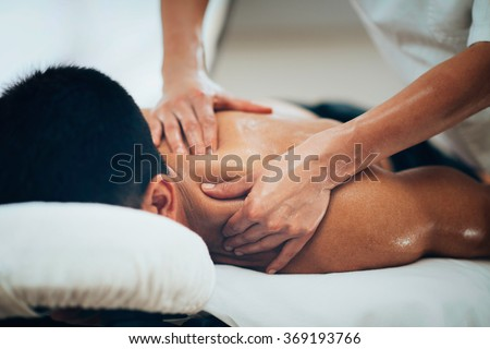 Sports massage. Massage therapist massaging shoulders of a male athlete, working with Trapezius muscle. Toned image - stock photo