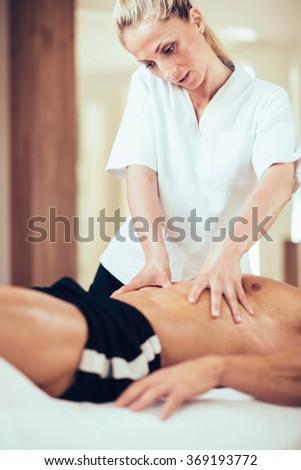 Sports massage. Massage therapist massaging stomach of a male athlete. Toned image - stock photo