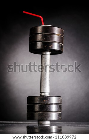 sports nutrition. metal barbell with red straw - stock photo