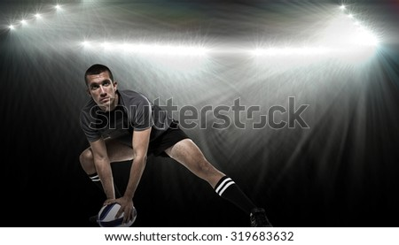 Sports player in black jersey stretching with ball against spotlight