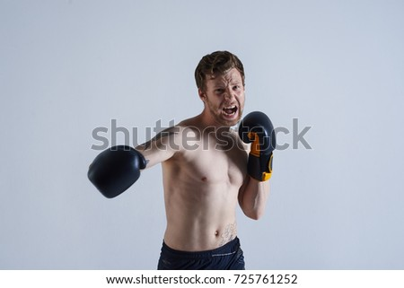 Sports, strength and determination concept. Professional angry kickboxer wearing black trunks and boxing gloves punching air in front of him as if defeating invisible enemy, his look full of fierce.