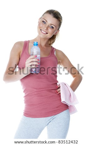 Sports time. Girl in the sports form with a bottle of water and a towel.