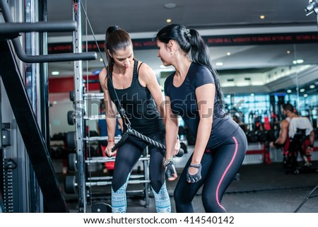 Sports training for women. Two women athletes doing exercise at the gym. - stock photo