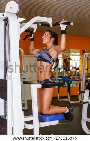 Sports woman doing exercises on power training apparatus in the gym. Pulling up on the horizontal bar. Gravitron Machine.
