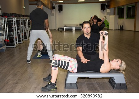 Sports woman doing exercises with dumbbells in the gym. Fitness.