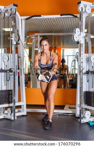 Sports woman doing the exercise for chest at the crossover machine in the gym. - stock photo