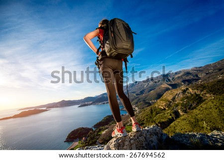 Sports woman in red vest with backpack standing on the top of mountain on the sunset.