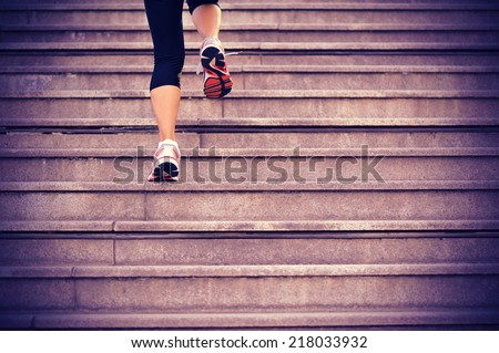 sports woman legs running up on stone stairs  - stock photo