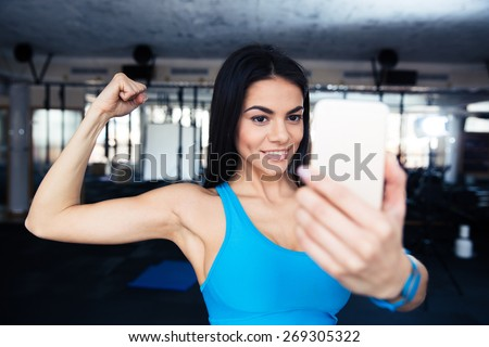 Sports woman making selfie on smartphone at gym - stock photo