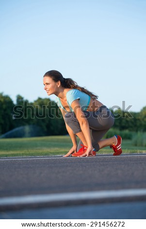 Sports woman ready to jog. Lady in red jogging shoes smiling isolated on nature background. - stock photo