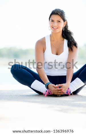 Sports woman stretching her legs outdoors and smiling - stock photo