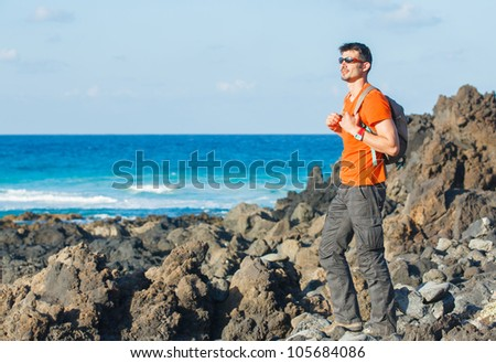 Sports young man with backpack. In the background of the sea - stock photo