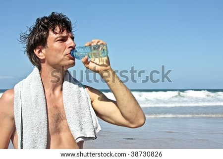 Sportsman drinking water after sporting at the beach - stock photo