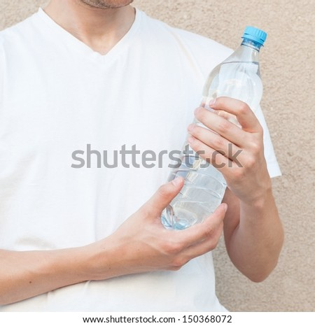 Sportsman holding a bottle of water - stock photo