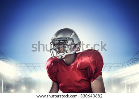 Sportsman holding American football while kneeling against rugby stadium