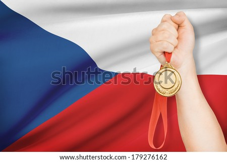 Sportsman holding gold medal with flag on background - Czech Republic - stock photo