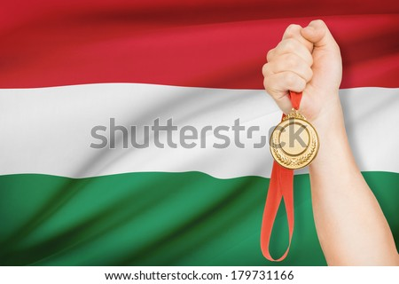 Sportsman holding gold medal with flag on background - Hungary - stock photo