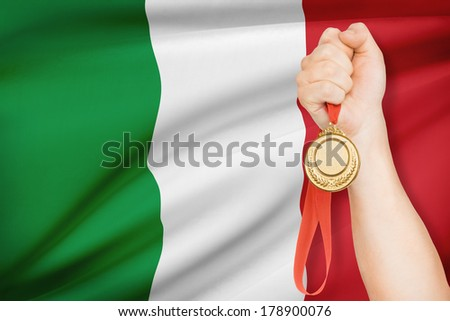Sportsman holding gold medal with flag on background - Italy - stock photo