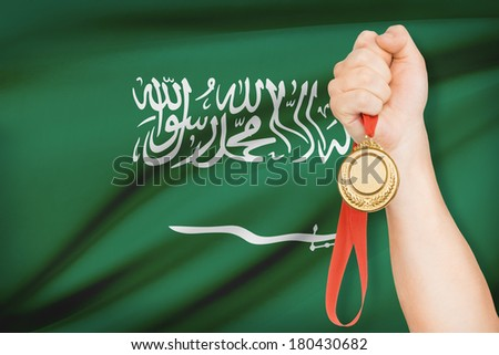 Sportsman holding gold medal with flag on background - Kingdom of Saudi Arabia - stock photo