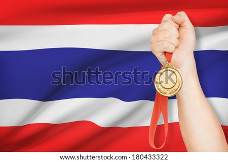 Sportsman holding gold medal with flag on background - Kingdom of Thailand - stock photo