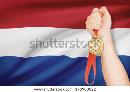 Sportsman holding gold medal with flag on background - Netherlands - stock photo
