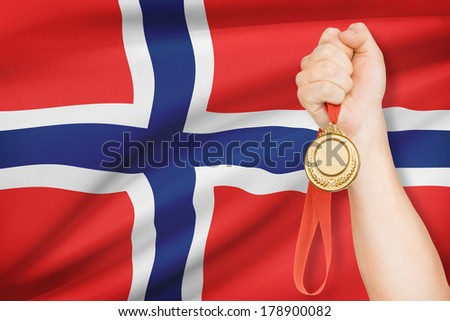Sportsman holding gold medal with flag on background - Norway - stock photo