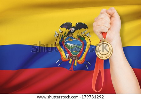 Sportsman holding gold medal with flag on background - Republic of Ecuador - stock photo