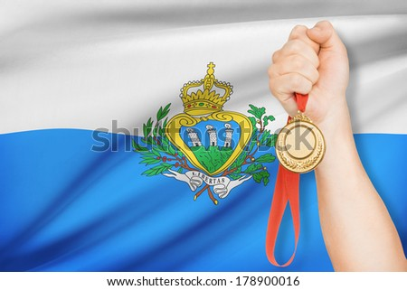 Sportsman holding gold medal with flag on background - San Marino - stock photo