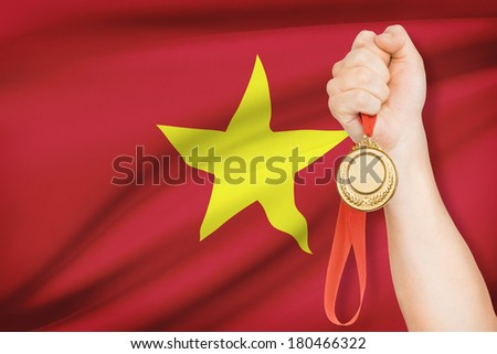Sportsman holding gold medal with flag on background - Socialist Republic of Vietnam - stock photo