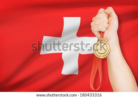 Sportsman holding gold medal with flag on background - Swiss Confederation - stock photo