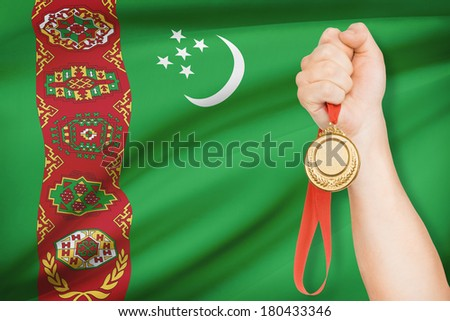 Sportsman holding gold medal with flag on background - Turkmenistan - stock photo
