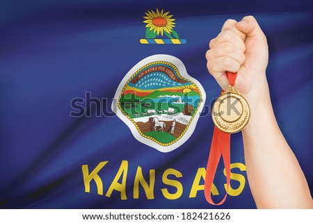 Sportsman holding gold medal with State of Kansas flag on background. Part of a series. - stock photo