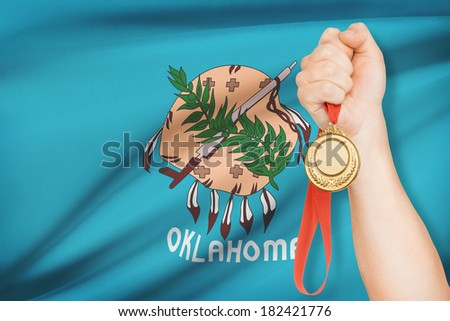 Sportsman holding gold medal with State of Oklahoma flag on background. Part of a series. - stock photo