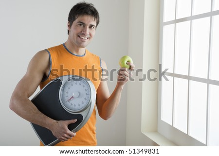 Sportsman holding scale and apple; concept: healthy lifestyle - stock photo