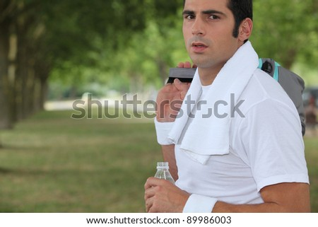 Sportsman in a park with a bottle of water - stock photo