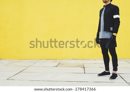 Sportsman in black wind breaker taking break with crossed hands standing on yellow wall background. Fit man resting after workout outdoors, runner resting after fitness training. - stock photo