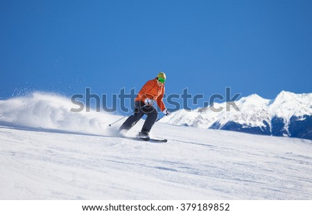 Sportsman in ski mask sliding fast while skiing view during sunny winter day on Krasnaya polyana ski resort and Caucasus mountains in Sochi, Russia