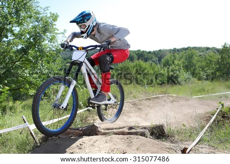 Sportsman in sportswear on a mountain bike rides in the extreme style of downhill